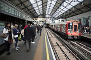 Tube train arriving at Earls Court underground station platform in London, England, United Kingdom.