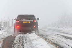 © Licensed to London News Pictures. 28/12/2020. Builth Wells, Powys, Wales, UK.  A motorist negotiates the B4520 Brecon Road through a wintry landscape on the Mynydd Epynt moorland near Builth Wells in Powys, Wales, UK. Photo credit: Graham M. Lawrence/LNP