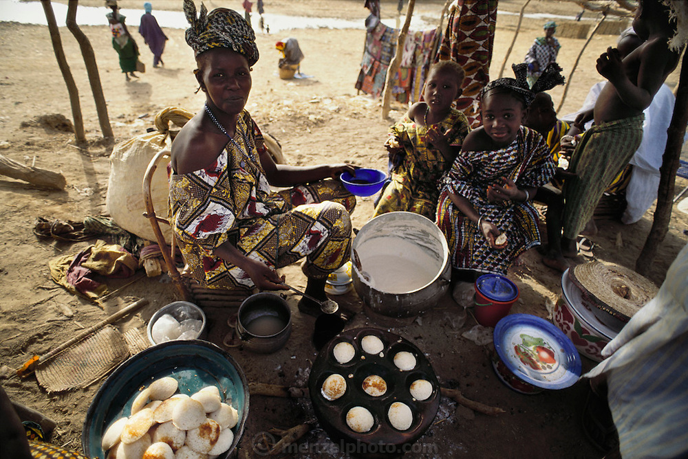 """A villager makes fried grain cakes called """"ngome"""" to sell at the Sunday market in Kouakourou, Mali. Kouakourou is the home village of the Natomo family lives in two mud brick houses near the banks of the Niger River. Material World Project."""