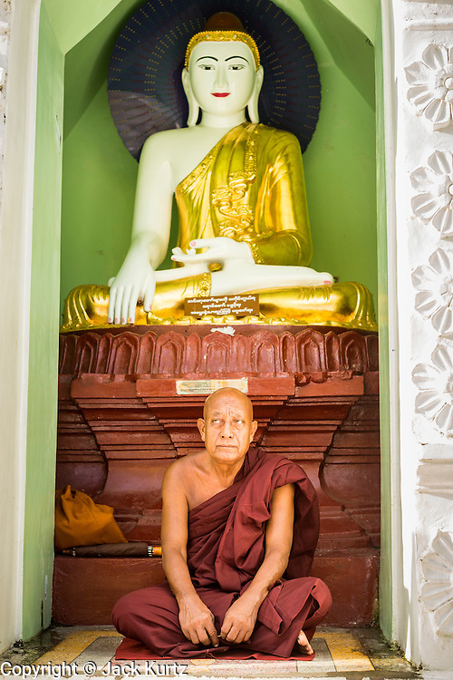 15 JUNE 2013 - YANGON, MYANMAR: A Buddhist monk prays at Shwedagon Pagoda. The Shwedagon Pagoda is officially known as Shwedagon Zedi Daw and is also called the Great Dagon Pagoda or the Golden Pagoda. It is a 99 metres (325ft) tall pagoda and stupa located in Yangon, Burma. The pagoda lies to the west of on Singuttara Hill, and dominates the skyline of the city. It is the most sacred Buddhist pagoda in Myanmar and contains relics of the past four Buddhas enshrined: the staff of Kakusandha, the water filter of Koṇāgamana, a piece of the robe of Kassapa and eight strands of hair fromGautama, the historical Buddha. The pagoda was built between the 6th and 10th centuries by the Mon people, who used to dominate the area around what is now Yangon (Rangoon). The pagoda has been renovated numerous times through the centuries. Millions of Burmese and tens of thousands of tourists visit the pagoda every year, which is the most visited site in Yangon.   PHOTO BY JACK KURTZ
