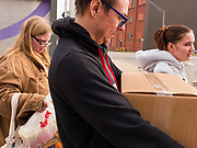 "26 MARCH 2020 - DES MOINES, IOWA: People walk away with food packages at a Des Moines Area Religious Council (DMARC) mobile pantry food distribution in the DART Central Station in Des Moines. DMARC is doing weekly food distribution at the transit station. They are using ""social distancing"" guidelines by asking clients to not get too close to their workers. DMARC used to let clients walk through mobile pantry to select groceries, but now clients wait while workers bags of foodstuffs. On Thursday morning, 24 March, Iowa reported 175 confirmed cases of the Coronavirus (SARS-CoV-2) and COVID-19. Restaurants, bars, movie theaters, places that draw crowds are closed until 07 April. The Governor has not ordered ""shelter in place""  but several Mayors, including the Mayor of Des Moines, have asked residents to stay in their homes for all but the essential needs. People are being encouraged to practice ""social distancing"" and many businesses are requiring or encouraging employees to telecommute.        PHOTO BY JACK KURTZ"