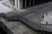 As workers in London largely remain working from home during the Coronavirus pandemic, a single figure walks across an urban street landscape of steps, road markings and traffic bollards in the City of London, the capital's financial district, on 4th September 2020, in London, England.
