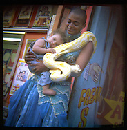 A snake charmer with her daughter before a show at Sideshows by the Seashore in Coney Island.