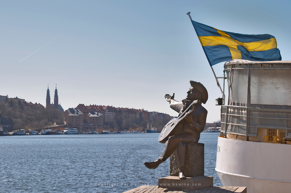 A statue on Riddarholmen of Evert Taube, the singer with his lute in front of Riddarfjarden and a typical white Stockholm Vaxholm boat with a Swedish flag blowing in the wind. Stockholm. Sweden, Europe.