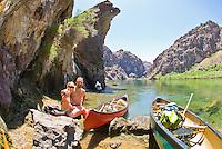 A couple enjoys the sun while on a paddle trip through The Black Canyon, Nevada.