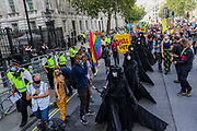 People some of them wearing face masks, hold placards and banners as they march along seven 'Oil Slicks' activists dressed in black-clads outside Downing Street on a march against 'ecocide' seeking to step up pressure on Shell and demand an end on fossil fuel extraction. Earlier on Tuesday, Sept 8, 2020 - Extinction Rebellion activists staged a performative protest enacting a crime scene outside Shell Headquarters in Jubilee Gardens, central London. Environmental nonviolent activists group Extinction Rebellion enters its 8th day of continuous ten days protests to disrupt political institutions throughout peaceful actions swarming central London into a standoff, demanding that central government obeys and delivers Climate Emergency bill. (VXP Photo/ Vudi Xhymshiti)