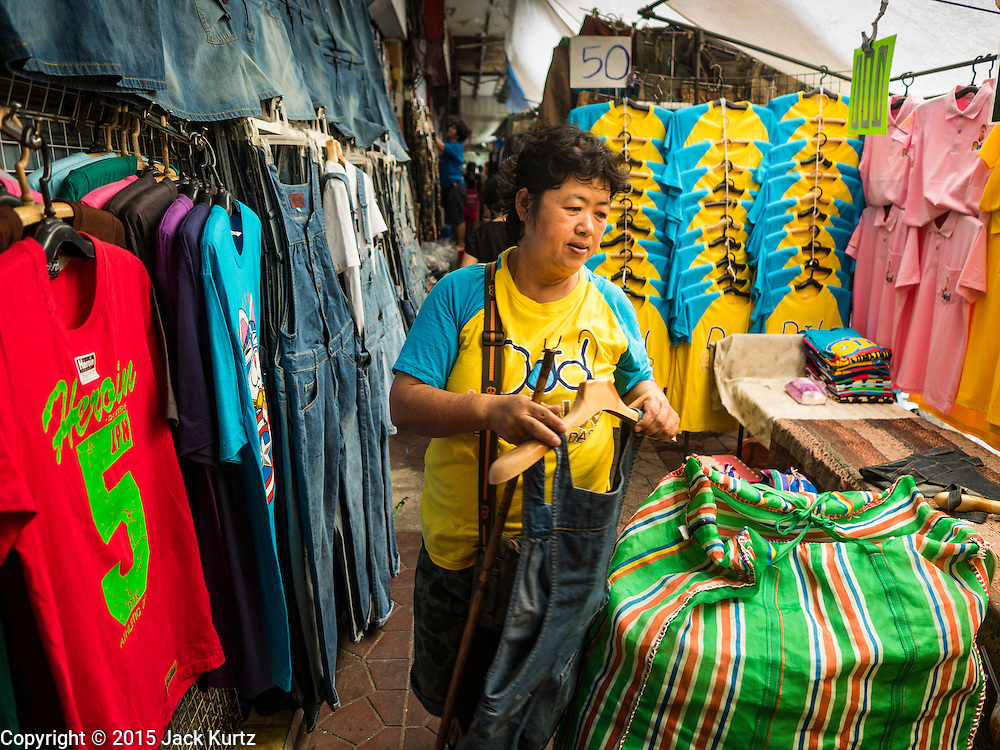 23 DECEMBER 2015 - BANGKOK, THAILAND: A vendor sets up her clothing shop in Banglampu Market. Banglamphu Market (also spelled Bang Lamphu) is close to Bangkok's backpacker haunts of Khao San Road. The market is a popular place for knock off designer clothes and street food. The market is an informal collection of street stalls and sidewalk vendors. Bangkok city officials have plans to evict the vendors, close the market and gentrify the neighborhood. This would follow closing similar markets on Maharat Road and Saphan Lek.       PHOTO BY JACK KURTZ