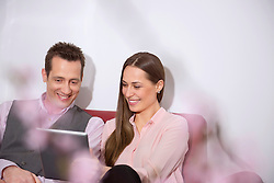 Young couple looking at tablet computer smiling