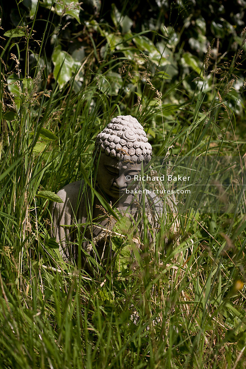 Buddha icon in long garden grass at the Rivendell Buddhist Retreat Centre, East Sussex, England.