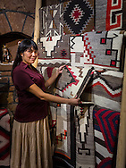 Savannah Means shows a Navajo rug at The Gallery, Cameron Trading Post, Cameron, Arizona