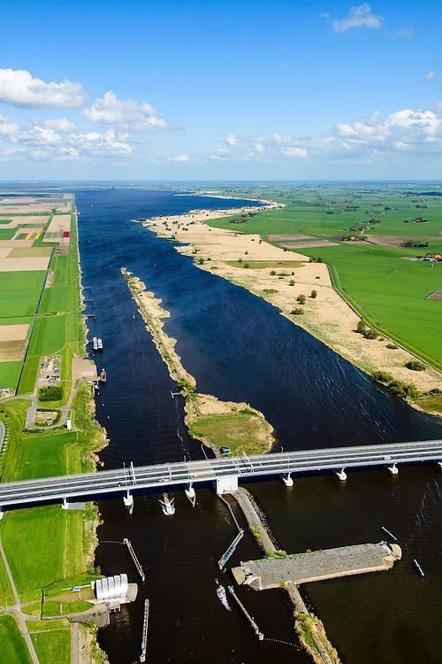 Nederland, Flevoland, Overijssel, Noordoostpolder, 07-05-2015. Ramspolbrug met N50, over de vaargeul het Ramsdiep. Naast de brug de balgstuw, onderdeel van Waterkering Kampen, tussen Ketelmeer en Zwarte Water (in de achtergrond). De balgstuw is een stormvloedkering en bestaat uit een opblaasbare dam of dijk, opgebouwd uit drie balgen. In niet-opgeblazen toestand liggen de balgen op de bodem. De witte betonenn toren in de voorgrond is  een voormalige luchtwachttoren.<br /> Ramspol bridge and Ramspol barrier, inflatable dike, between Ketelmeer and Black Water. The Balgstuw (bellow barrier) is a storm barrier and consists of an inflatable dam or dyke, composed of three bellows. Usually, each bellow rests on the bottom of the water<br /> luchtfoto (toeslag op standard tarieven);<br /> aerial photo (additional fee required);<br /> copyright foto/photo Siebe Swart