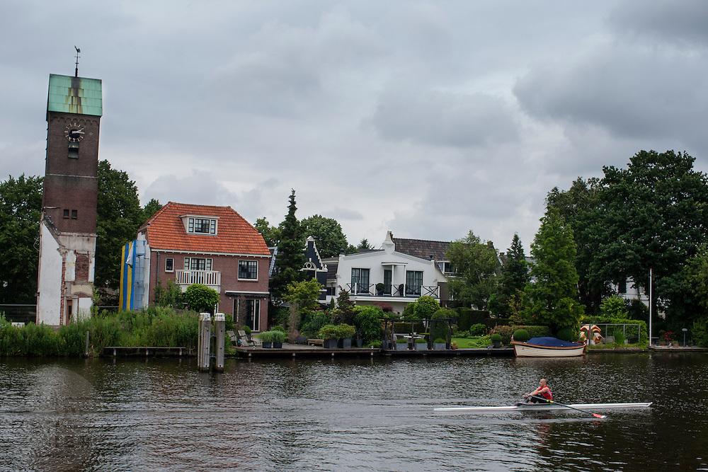 Een man vaart met een kano over de Amstel bij Amstelveen.<br /> <br /> A man is canoeing at the Amstel bar Amstelveen.
