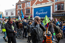 London, UK. 9th February, 2019. A passerby covers his ears during drumming by activists from Extinction Rebellion blocking Kingsland Road in Dalston as part of a 'Saturday street party' intended as a means of engagement around climate change and environmental issues with the local community.