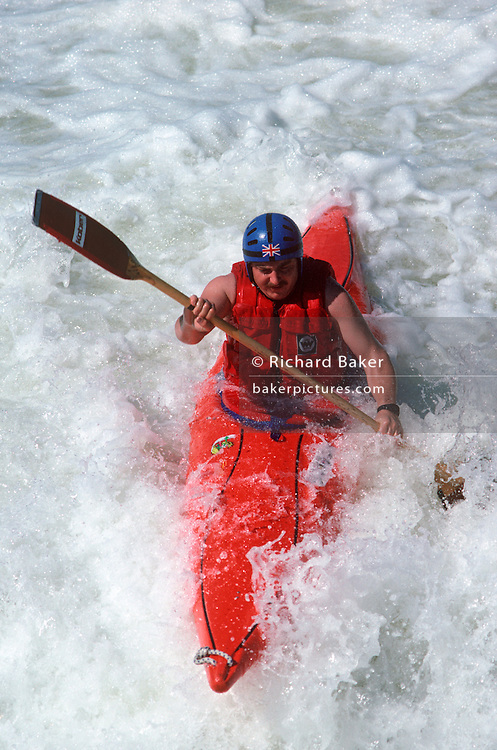 A British canoeist negotiates a whitewater course as spray froths around his kayak.