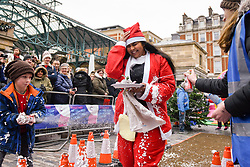 © Licensed to London News Pictures. 08/12/2018. LONDON, UK.  A competitor takes part in The 38th Great Christmas Pudding Race in Covent Garden, raising funds for Cancer Research as well as having a lot of festive fun.  Photo credit: Stephen Chung/LNP