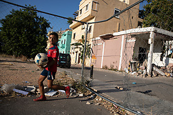 © Licensed to London News Pictures. 16/08/2020. Beirut, Lebanon. A boy runs with a football in the Karantina district of Beirut which has been badly destroyed following the huge explosion in Beirut Port on 4 August. Photo credit : Tom Nicholson/LNP
