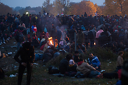 Licensed to London News Pictures. 27/10/2015. Sentilj, Slovenia. Migrants warm themselves around a fire as they wait for buses at a border crossing between Slovenia and Austria. Photo: Marko Vanovsek/LNP