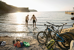 Men in cycling shorts standing in water at beach