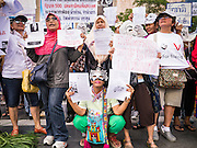 """09 JUNE 2013 - BANGKOK, THAILAND: Members of the White Mask protest movement gather on the plaza in front of Central World in Bangkok. The White Mask protesters wear the Guy Fawkes mask popularized by the movie """"V for Vendetta"""" and the protest groups Anonymous and Occupy. Several hundred members of the White Mask movement gathered on the plaza in front of Central World, a large shopping complex at the Ratchaprasong Intersection in Bangkok, to protest against the government of Thai Prime Minister Yingluck Shinawatra. They say that her government is corrupt and is a """"puppet"""" of ousted (and exiled) former PM Thaksin Shinawatra. Thaksin is Yingluck's brother. She was elected in 2011 when her brother endorsed her.     PHOTO BY JACK KURTZ"""