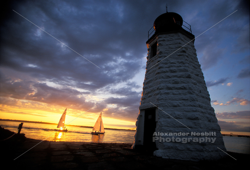 USA, Newport, RI - Sheilds sailboat passes infront of setting sun near Green Light lighthouse on gaot Island in Narragansett bay .