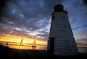 USA, Newport, RI - Sheilds sailboat passes infront of setting sun near Green Light lighthouse on gaot Island in Narragansett bay .