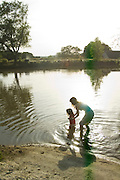 A woman helps a toddler as they wade through a pond