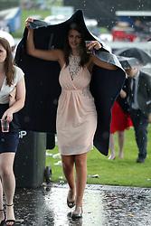 A female racegoer shelters from the rain on Ladies Day during the 2017 Investec Epsom Derby Festival at Epsom Racecourse, Epsom.