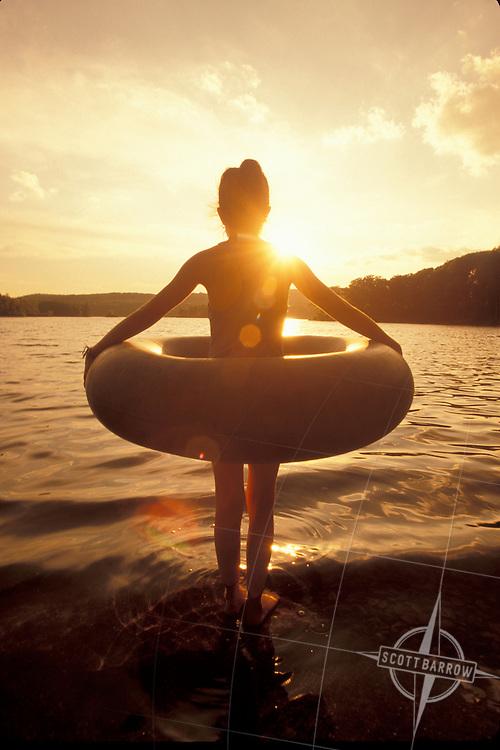 Girl holding innertube in lake