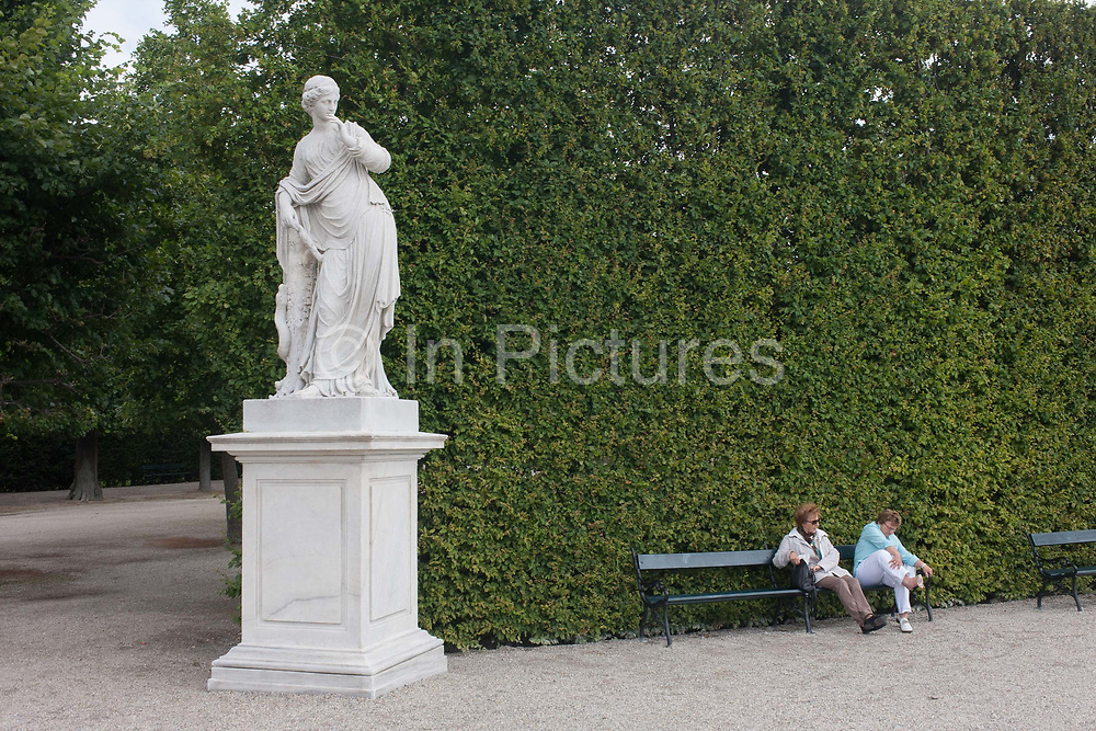 Ladies sit to rest on a bench with sore feet beneath a statue at Schloss Schonbrunn palace on 27th June 2016, in Vienna, Austria. Schonbrunn is a former imperial summer residence located in Vienna, Austria. The 1,441-room Baroque palace is one of the most important architectural, cultural, and historical monuments in the country. Since the mid-1950s it has been a major tourist attraction. The history of the palace and its vast gardens spans over 300 years, reflecting the changing tastes, interests, and aspirations of successive Habsburg monarchs.