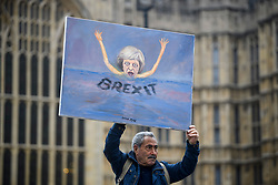 © Licensed to London News Pictures. 15/11/2018. London, UK. Artist KAYA MAR holds up artwork depicting British Prime Minister Theresa May drowning In Brexit, outside the Houses of Parliament in Westminster, the day after Cabinet agreed to back Prime Minister Theresa May's deal on Brexit. Photo credit: Ben Cawthra/LNP
