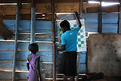 Phiona Mutesi, right, a 14-year-old chess prodigy, at the Agape Church inside Katwe, the largest slum in Kampala, Uganda, Dec. 8, 2010. There are only seven chessboards at the church, and chess pieces are so scarce that sometimes an orphan pawn must stand in for a king. Mutesi lives in the slums of Uganda and is just now learning to read. But her instincts have made her a player to watch in international chess. Mutesi, a naturally talented chess player is coached by Robert Katende of Sports Outreach Ministry. The chess club meets at the Agape Church.