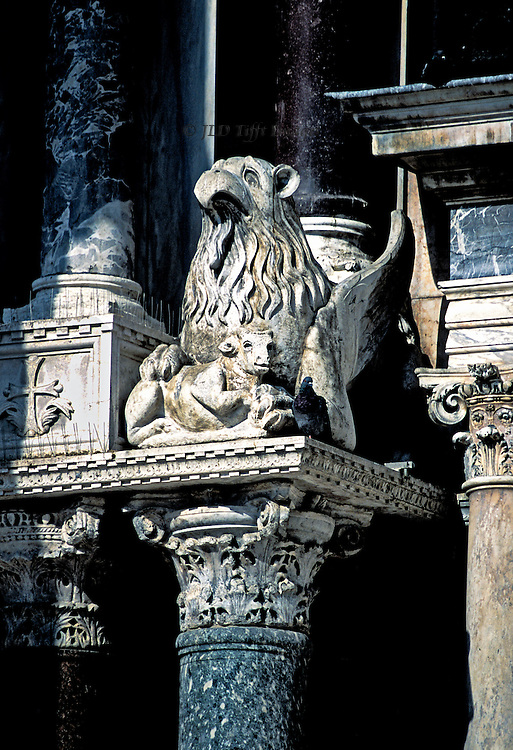 Statue of a winged griffin ( or gryphon - lion's body, head and wings of an eagle)  with claws resting on a serene lamb in front of it, both atop a Byzantine column,  Exterior of San Marco Basilica, Venice..