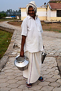 Natrajan walks back from milking the cows in the dairy with a churn of milk. Tamaraikulum Elders village, Tamil Nadu, India