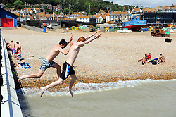 © Licensed to London News Pictures. 17/07/2018<br /> Hastings, UK.<br /> Teenagers jumping off a small pier near the fishing boats.<br /> Hot heatwave weather in Hastings on the seafront as people enjoy their day.<br /> Photo credit: Grant Falvey/LNP