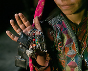 Wakhi woman shows the pendants on her dress. House of Abena. In the village of Qala-e Ust. The traditional life of the Wakhi people, in the Wakhan corridor, amongst the Pamir mountains.