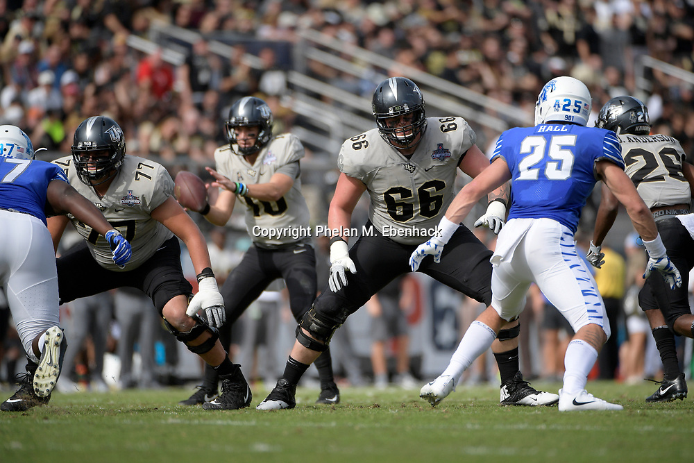 Central Florida offensive lineman Aaron Evans (66) and offensive lineman Jake Brown (77) set up to block in front of Memphis defensive lineman Emmanuel Cooper (97) and defensive back Austin Hall (25) during the first half of the American Athletic Conference championship NCAA college football game against Memphis Saturday, Dec. 2, 2017, in Orlando, Fla. (Photo by Phelan M. Ebenhack)