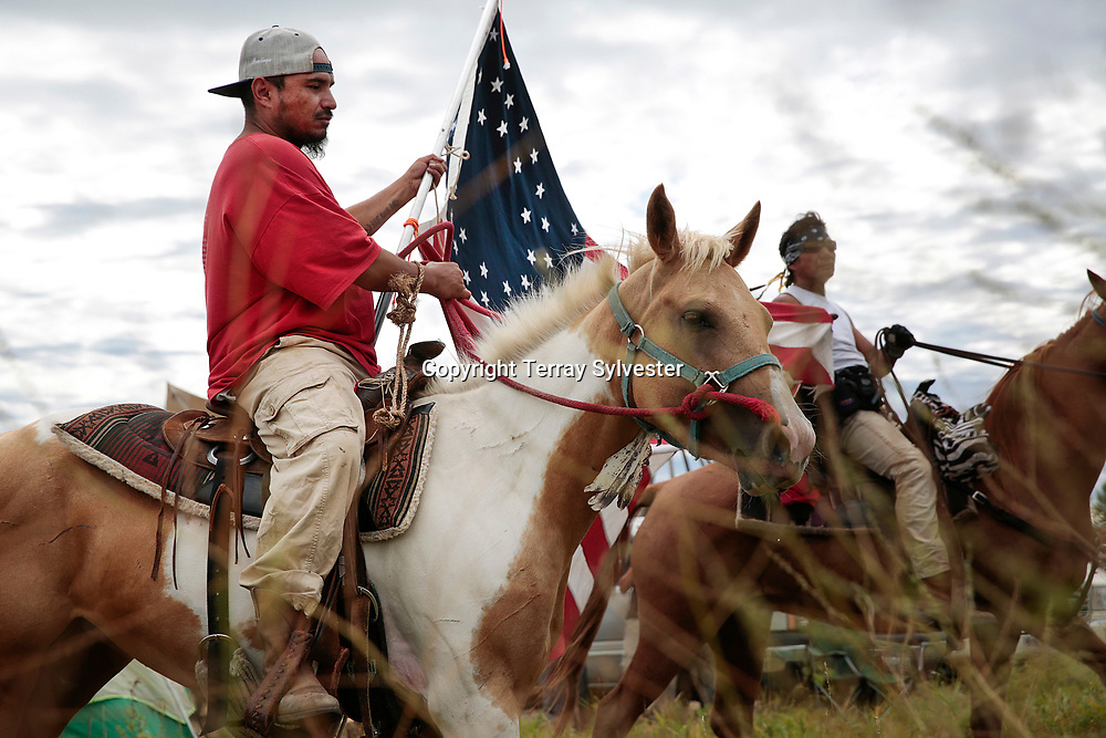 While carrying a replica of the flag lost by U.S. cavalry at the historic Battle of the Little Bighorn, Christopher Dion (left) of the Crow Creek Sioux Tribe and Frank Archambault of the Standing Rock Sioux Tribe ride through the opposition camp against the Dakota Access oil pipeline on September 8, 2016. Cannon Ball, North Dakota, United States.