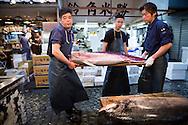 Katsuhiko Watanabe, Hideto Takeda and Masakazu Sato carrying a tuna at the Tsukiji Market, Tokyo, Japan