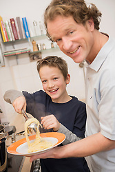 Father and son eating spaghetti in kitchen