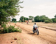 """NUBA MOUNTAINS, SUDAN – JUNE X, 2018: A view of city life in Kouda, the cultural center of Hieban County.<br /> <br /> In 2011, the government of Sudan expelled all humanitarian groups from the country's Nuba Mountains. Since then, the Antonov aircraft has terrorized the Nuba people, dropping more than 4,080 bombs on hospitals, schools, marketplaces and churches. Today, vestiges of the Antonov riddle the landscapes of daily life, where more than 1 million Nuba live in famine conditions – quietly enduring the humanitarian blockade intended to drive them out of the region. The skies are mostly clear. Yet the collective memory of the bombings remains an open wound, and the Antonov itself a persistent threat. So frequent were the attacks that the Nuba nicknamed the high flying aircraft and its dismal hum: """"Gafal-nia ja,"""" they would declare, running to the hillsides. """"The loss of appetite has come."""""""