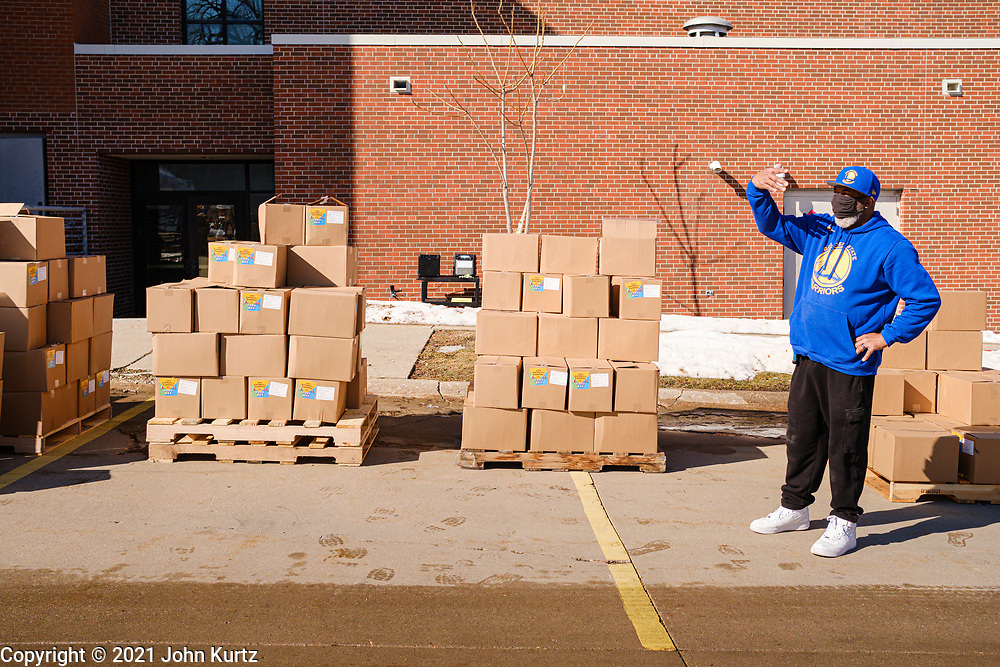 """27 FEBRUARY 2021 - DES MOINES, IOWA: A volunteer directs traffic during an emergency food distribution at the John R. Grubb Community YMCA in Des Moines. The food distribution was organized by Farmers to Families and the YMCA. They had 1,000 boxes of emergency rations which included fresh fruit and vegetables, yogurt, chicken and hot dogs. They also had 1,000 gallons of milk. The neighborhood around the YMCA is a """"food desert,"""" with no nearby grocery stores that sell healthy food. Food bank use in Iowa is up more than 60% since the start of the Coronavirus pandemic. Food bank officials estimate that 4 in 10 users are new users of emergency food pantries.        PHOTO BY JACK KURTZ"""