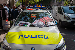 A police car is left littered with posters after demonstrators gathered outside India House in London to show support for Kashmiris and to protest against occupation and oppression by India in Kashmir.<br /> <br /> Police worked to keep the protesters and counter protesters apart through use of barriers, mounted police and lines of police.<br /> <br /> Richard Hancox | EEm 15082019