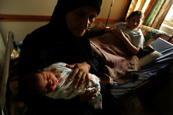 "Inas, the newborn daughter of Jawaher Ali Salah, 19, is comforted by her grandmother Jamila Abu Sarhan, inside the Shepherd's Field Hospital in Bethlehem, Palestinian Territories, Nov. 15, 2004. The baby was born via cesarian section when she was breeched. Once the baby goes home and the family has gathered enough money, they will slaughter one sheep. When a boy is born, two sheep are killed in celebration. ""We are very poor, so all we can do right now is give sweets to our neighbors,"" said the father Ali Salah Tambre, 28. Ali used to work as a laborer in Israel but has been unemployed since the beginning of the Second Intifada."