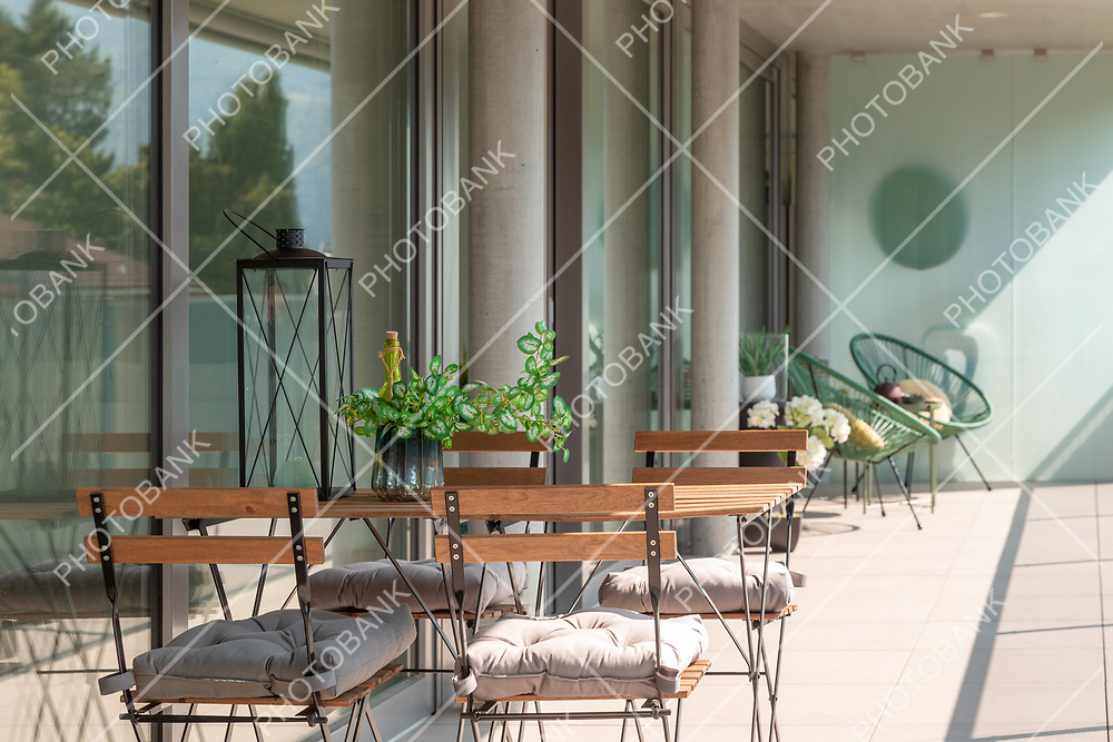 Modern house terrace with wooden table and chairs. A seedling, a bottle and a lantern on the table. Sunny day in summer.