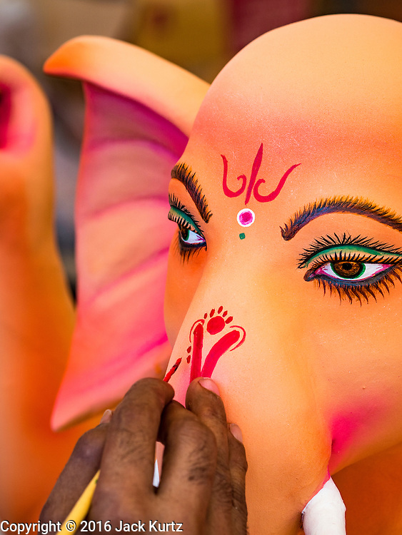 """29 AUGUST 2016 - BANGKOK, THAILAND:  A craftsman at the Vishnu Temple in Bangkok paints the face of a statue of Ganesha, an important Hindu deity known as the """"overcomer of obstacles."""" Ganesha Chaturthi is the Hindu festival celebrated on the day of the re-birth of Lord Ganesha, the son of Shiva and Parvati. Ganesha is widely revered as the patron of arts and sciences and the deva of intellect and wisdom. The last day of the festival is marked by the immersion of the deity in nearby bodies of water. The immersion symbolizes the cycle of creation and dissolution in nature. The deities made at the Vishnu Temple in Bangkok will be submerged in rivers and streams across Thailand at several Ganesha festivals held in September.           PHOTO BY JACK KURTZ"""