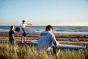 Family at St Ouen's Bay, Jersey watching the surf and waxing a surfboard, getting ready to go surfing