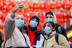 © Licensed to London News Pictures. 26/01/2020. London, UK.  Members of public are seen wearing face masks as they take a selfie in Chinatown in central London, following the outbreak of Coronavirus in China which has killed 41 people. Photo credit: Dinendra Haria/LNP
