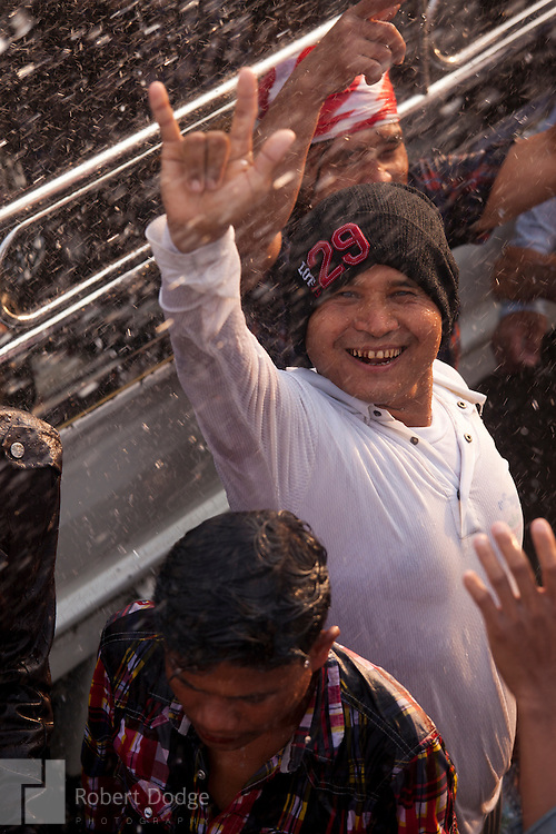 Mandalay, Myanmar- April 14, 2013: A young man expresses his excitement during Myanmar's Thingyan Water Festival. Thingyan is held in April, one of the hottest months of the year in Myanmar. The water festival marks the country's New Year celebration and the festival includes lots of drinking, singing, dancing and theater. Wherever you are you are likely to get doused with water as the Burmese see this as a cleansing of the previous year's sins and bad luck and a blessing for good luck and prosperity in the year ahead. In the major cities of Mandalay and Yangon, large platforms are erected along major roadways and are equipped with high powered water hoses. The platforms, sponsored by large corporate donors, also have dance stages and play the latest pop and hip hop music. Thousands of residents pour into the streets by foot, motorbike and flatbed truck to get hosed under the platforms while they drink and dance. Many of the young celebrants wear their best clubbing clothes. And many of the party goers are men, having left their wives and girlfriends at home.