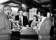One of the most flamboyant and controversial heroes in the history of soccer, Derek Dougan signs copies of his autobiography, Doog, for customers at Hodges Figgis, Stephen's Court, Dublin. Photo shows one of the first customers, Peter Moynihan of Sandyford, County Dublin, as well as Robert Twigg, Manager, Hodges Figgis, and Norma Doyn, cashier.<br /> 16 April 1980