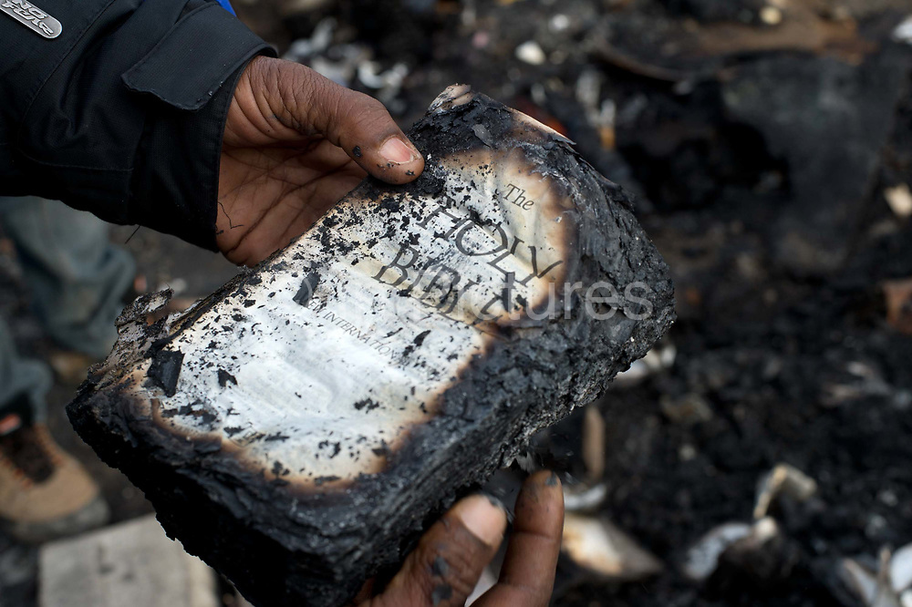 France. Refugees. Calais. So-called Jungle camp .  A charred bible amongst the  mess from the fire the night before (Saturday  21st November 2015 )